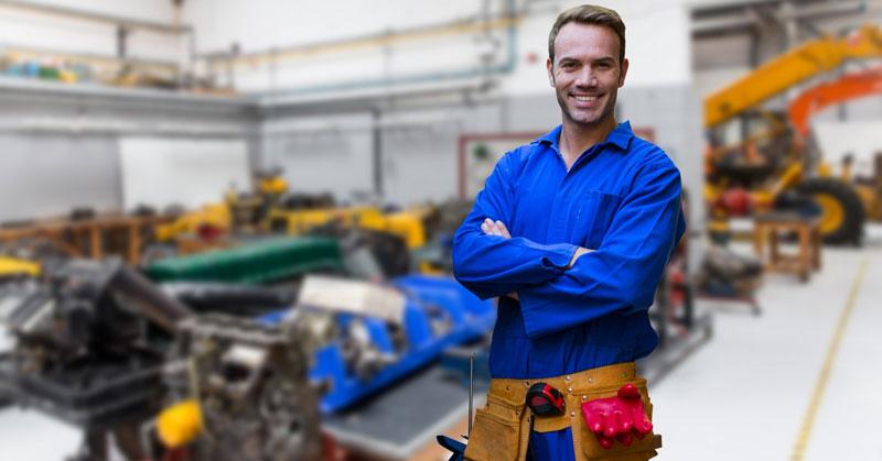 Homme se tenant debout derrière une usine de fabrication de métal